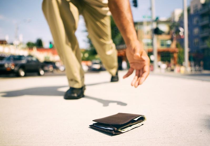 Un homme ramasse un portefeuille au sol