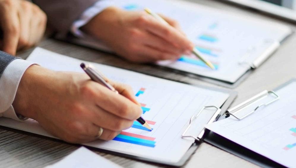Mains qui tiennent un stylo et qui écrivent sur un graphique