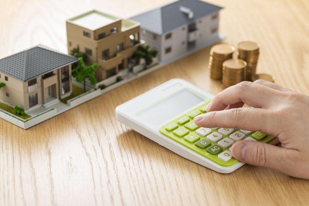 Une maquette d'une maison avec une calculatrice et des pièces de monnaie