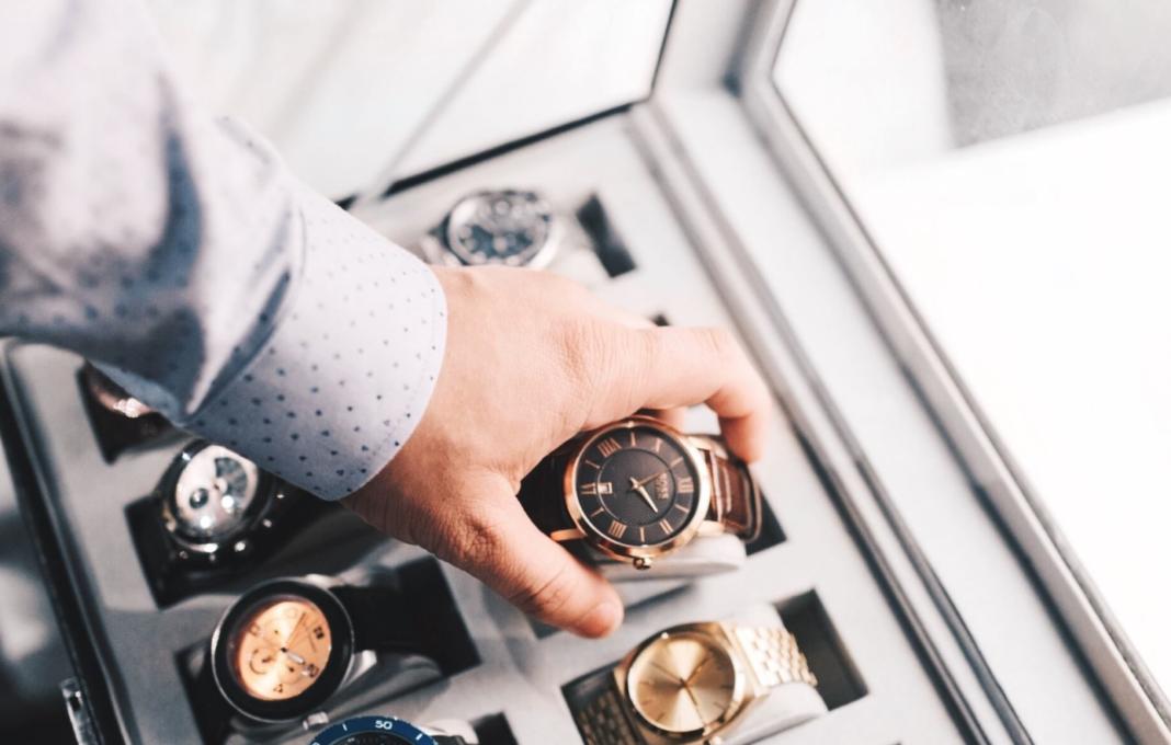 main homme saisit montre de luxe dans un coffret