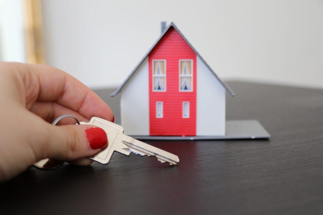 main de femmes ongles vernis rouge tient clé de maison immobilier